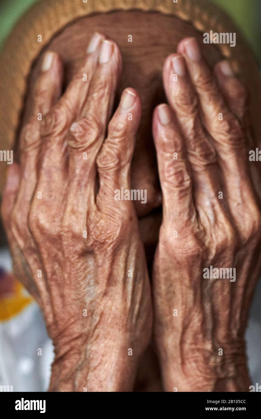 Portrait Of An Elderly Malay Female Covering Her Face With Her Wrinkled Hands Stock Photo Alamy