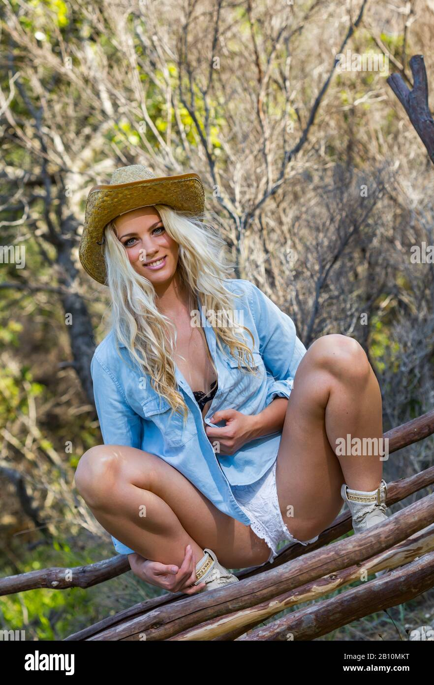 Squatting squat squatter wide apart spread knees legs smiling looking at camera eyeshot eye eyes contact countrygirl country-girl stetson Western hat Stock Photo