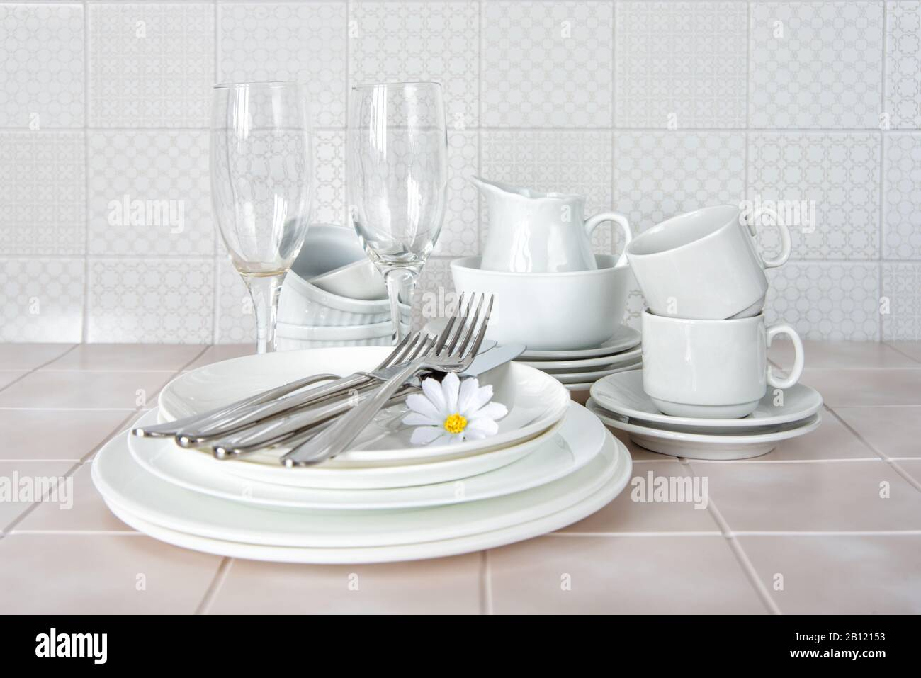 Stack of white porcelain plates, tea cups and wine glasses on the