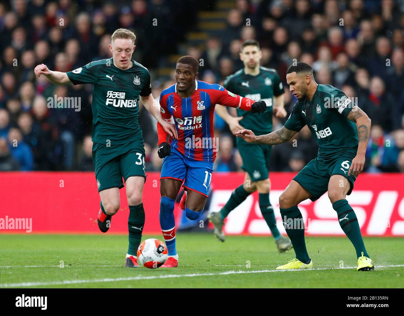 Selhurst Park, London, UK. 22nd Feb, 2020. English Premier League Football, Crystal Palace versus Newcastle United; Wilfried Zaha of Crystal Palace being challenged by Sean Longstaff and Jamaal Lascelles of Newcastle United - Strictly Editorial Use Only. No use with unauthorized audio, video, data, fixture lists, club/league logos or 'live' services. Online in-match use limited to 120 images, no video emulation. No use in betting, games or single club/league/player publications Credit: Action Plus Sports/Alamy Live News Stock Photo