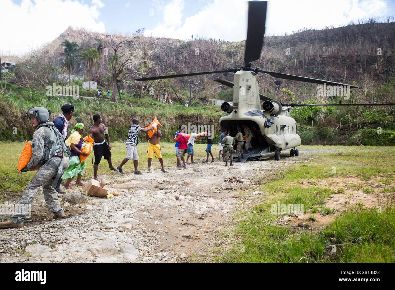 U.S. Army Sgt. Delton Reynolds, left, a flight engineer with Joint Task Force - Leeward Islands, joins a chain with local residents and members of the Jamaican Defence Force to unload relief supplies from a CH-47 Chinook helicopter at Wotten Waven, Dominica, Oct. 3, 2017. The aircraft delivered rice and kitchen sets from the U.S. Agency for International Development to the community. At the request of USAID, JTF-LI has deployed aircraft and service members to assist in delivering relief supplies to Dominica in the aftermath of Hurricane Maria. The task force is a U.S. military unit composed of Stock Photo