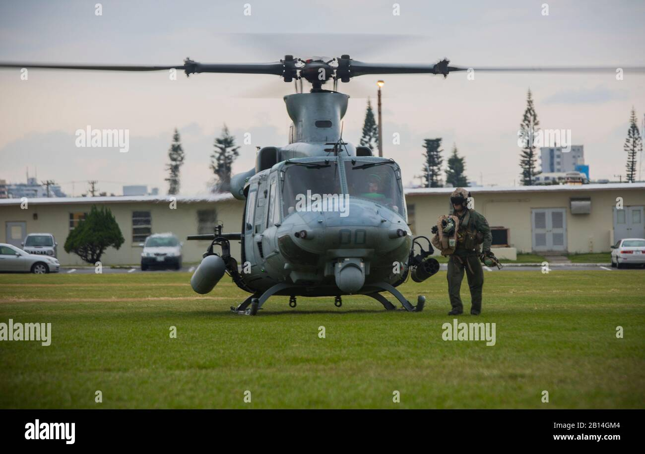 """U.S. Marine Corps crew chief unloads flight gear from a UH-1Y Venom at Camp Foster, Okinawa, Japan, Dec. 15, 2017. Marine Light Attack Helicopter Squadron 369 provided Lt. Gen. Brian D. Beaudreault, deputy commandant of plans, policies and operations, a flight around the Okinawa Prefecture to assess the service quality of the Marine Corps chowhalls. The """"gunfighters'"""" readiness to act upon a moment's notice is crucial to maintaining a stronger, more capable forward deployed force in the Indo-Asia-Pacific region. HMLA-369, Marine Aircraft Group 39, 3rd Marine Aircraft Wing, is currently forward Stock Photo"""