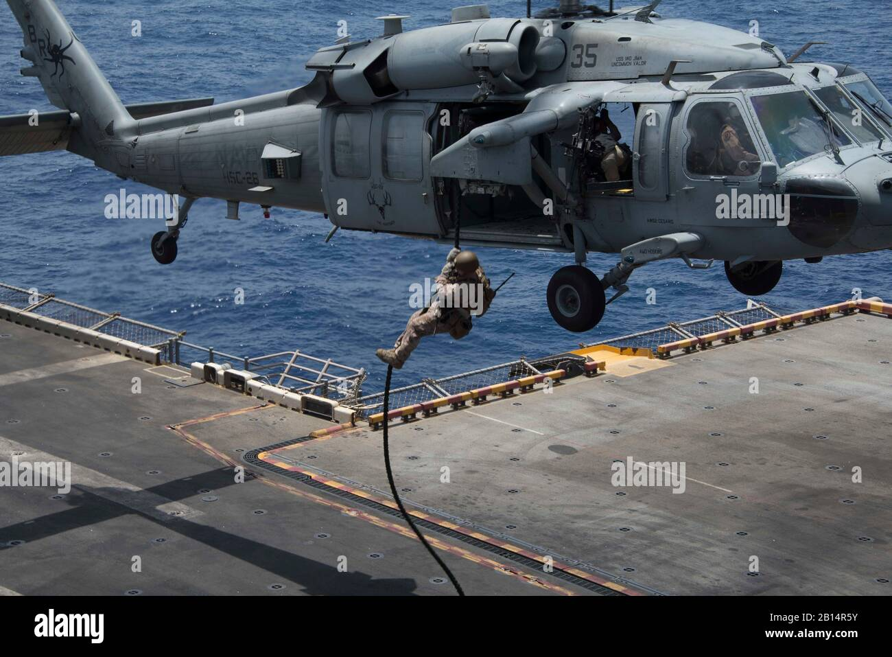 A U.S. Marine assigned to the 26th Marine Expeditionary Unit, fast ropes from an MH-60S Sea Hawk helicopter attached to Helicopter Sea Combat Squadron (HSC) 28, to the flight deck of the Wasp-class amphibious assault ship USS Iwo Jima (LHD 7), during a fast rope exercise in the 5th Fleet Area of Operations, May 21, 2018. The Iwo Jima was deployed to the U.S. 5th Fleet area of operations in support of maritime security operations to reassure allies and partners, and preserve the freedom of navigation and the free flow of commerce in the region. (U.S. Navy photo by Mass Communication Specialist Stock Photo