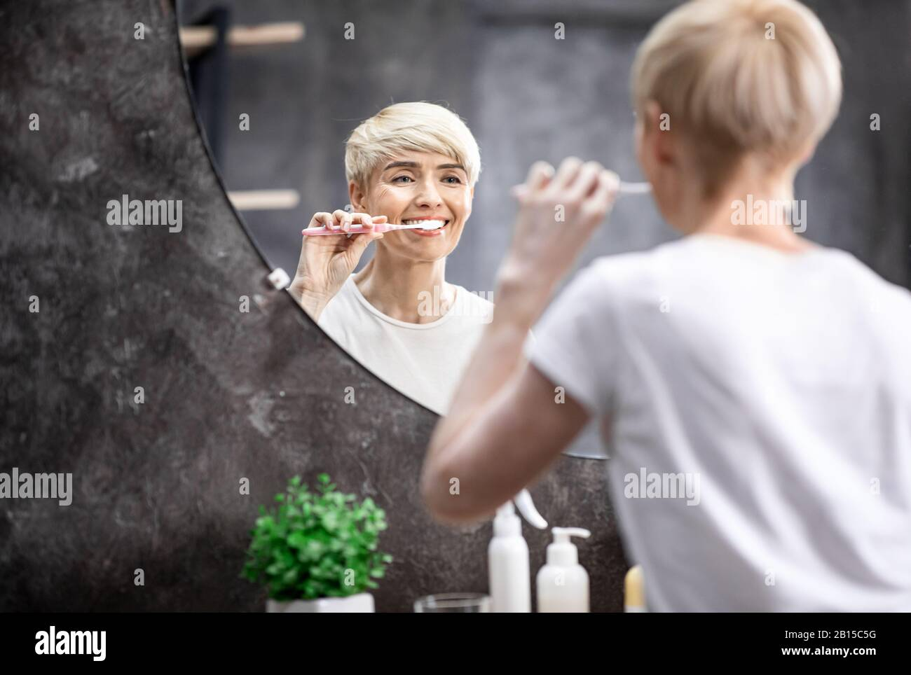 Lady Brushing White Teeth Standing In Bathroom In The Morning Stock Photo