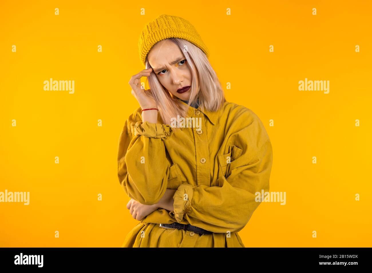 Young upset woman with white hair having headache, studio portrait. Stock Photo