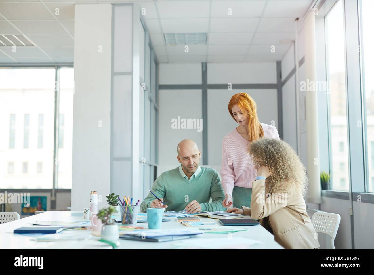 Group of three business people discussing documents while working at table in office, copy space Stock Photo