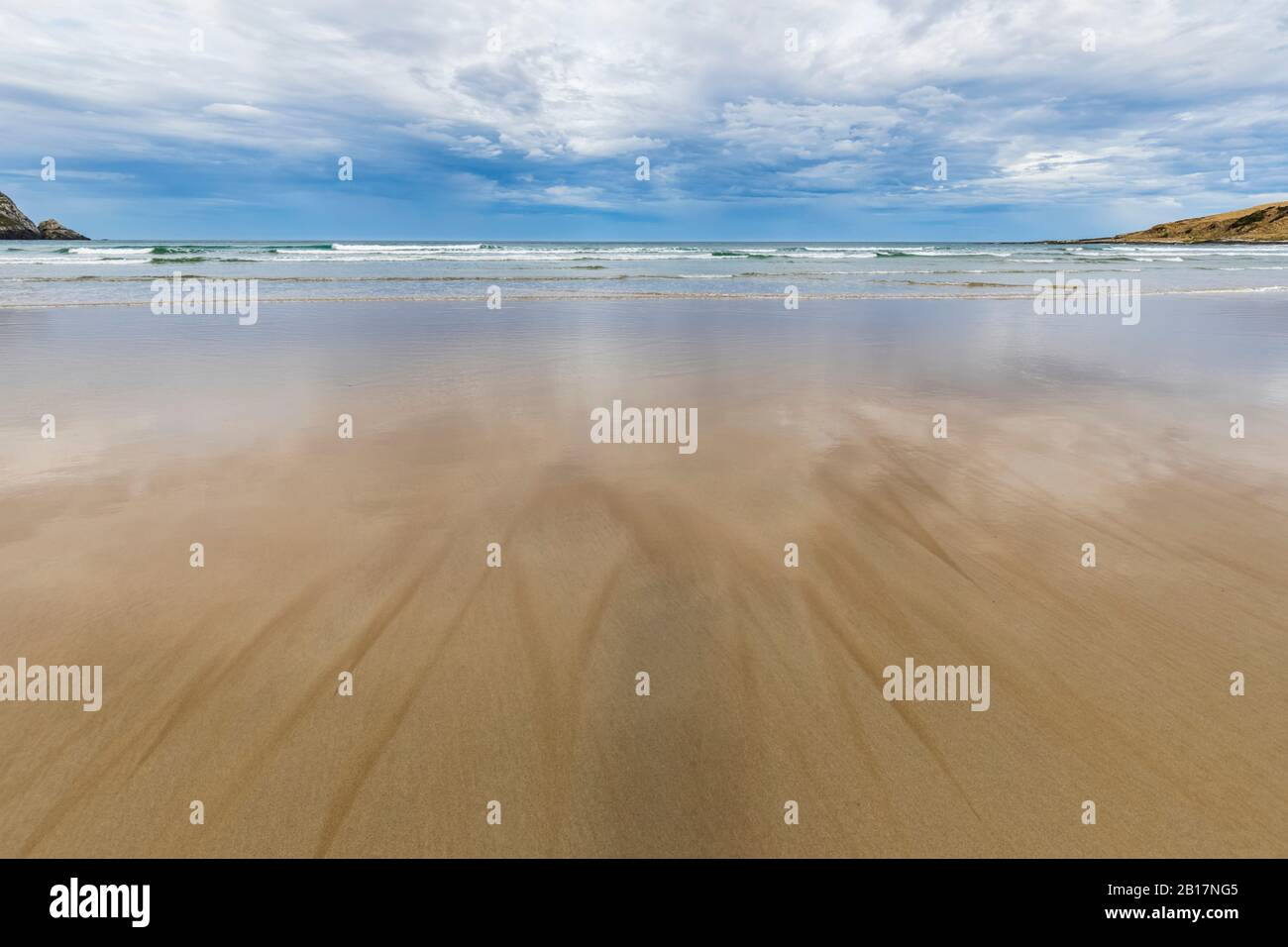 New Zealand, Cloudy sky over sandy coastal beach ofPurakaunuiBay Stock Photo