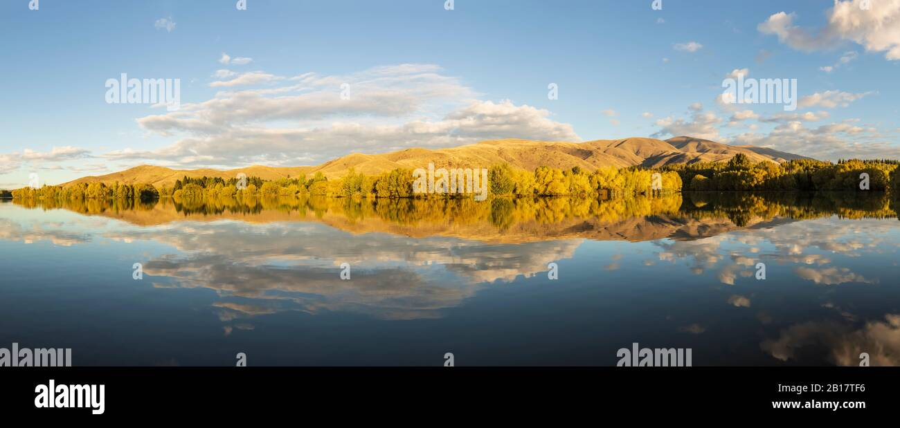 New Zealand, Franklin District, Glenbrook, Forested hills reflecting in Wairepo Arm lake in autumn Stock Photo