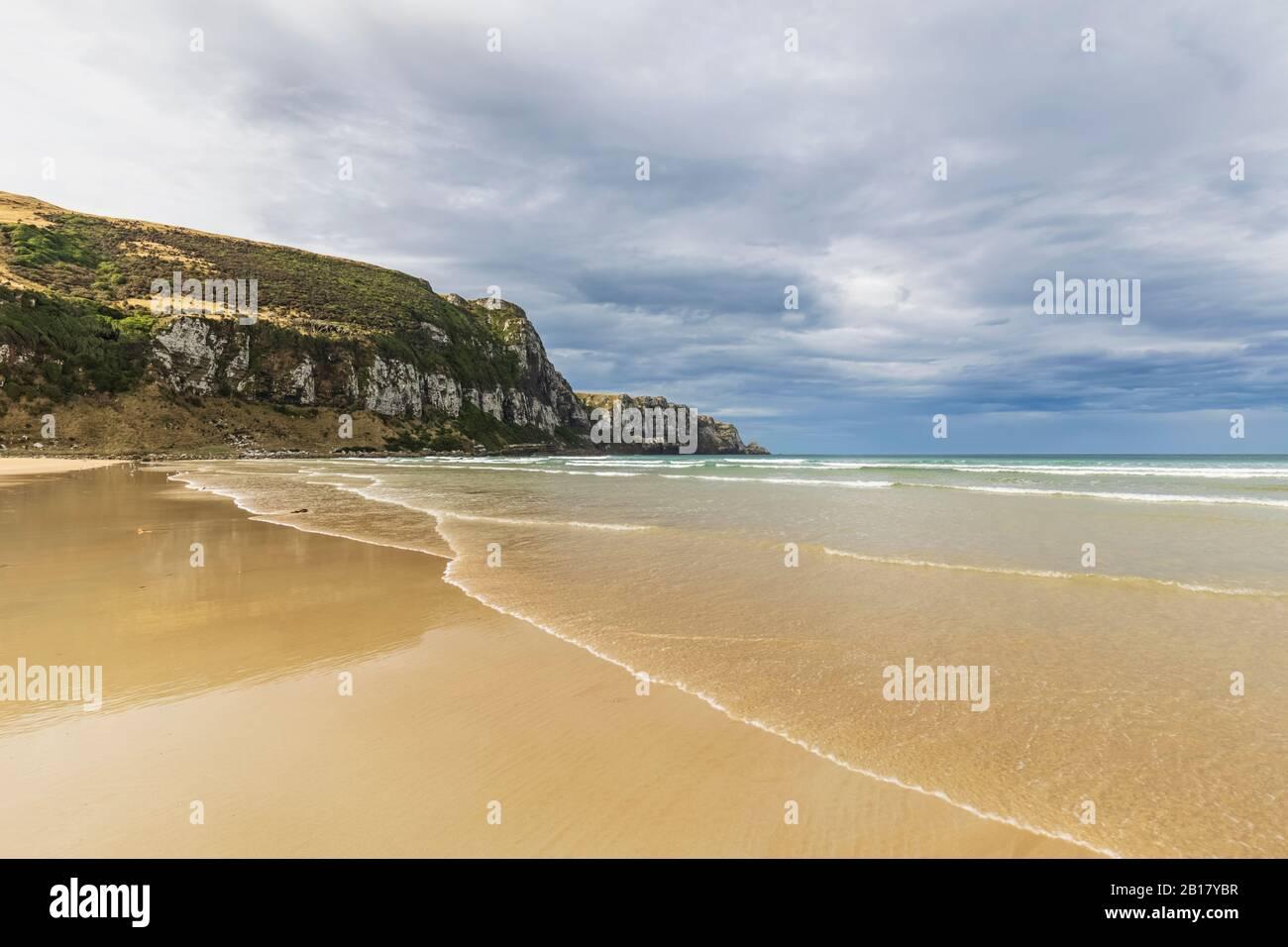 New Zealand, Cloudy sky over sandy coastal beach of Purakaunui Bay Stock Photo