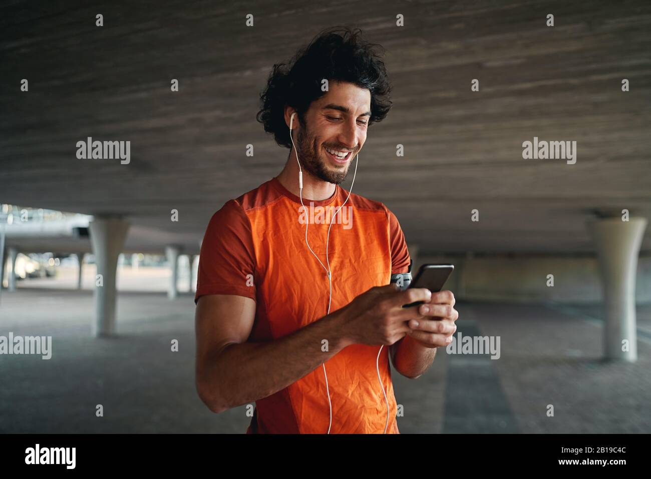 Portrait of a smiling young male runner standing under the concrete bridge with earphone in his ears typing on a smart phone Stock Photo