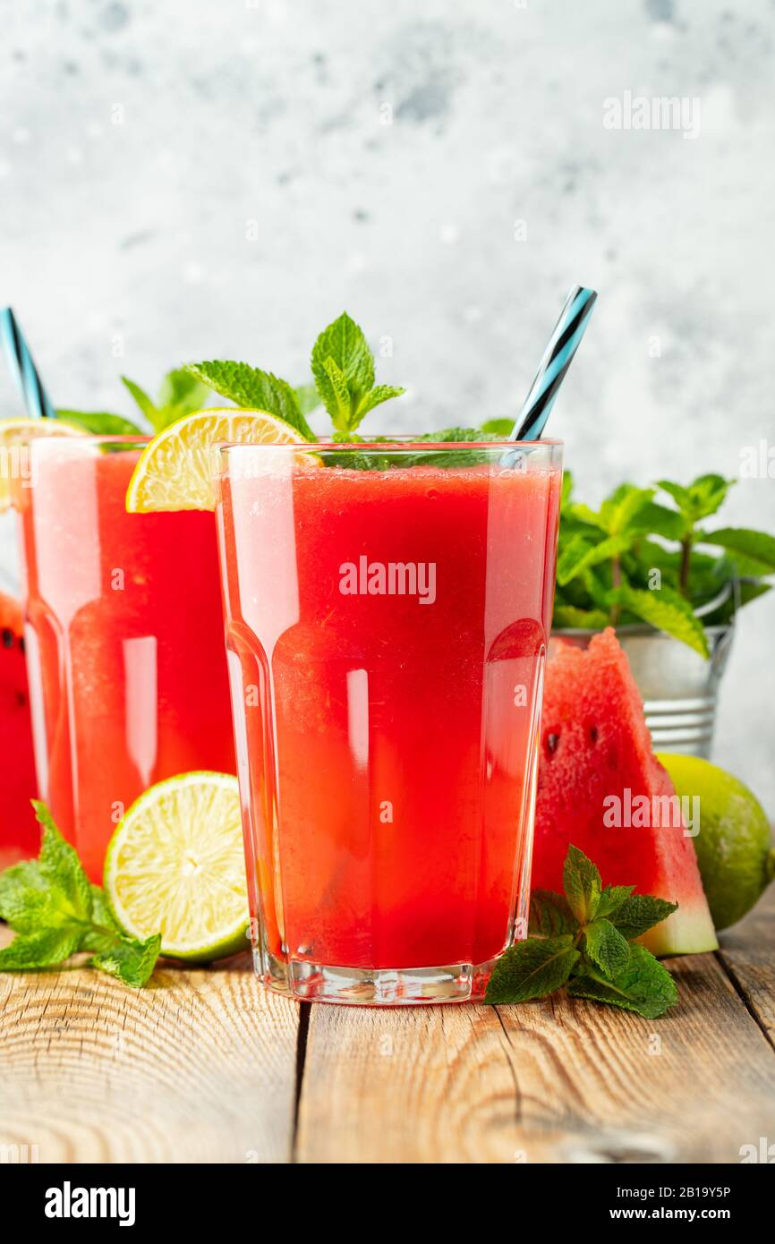 Watermelon slushie with lime and mint, summer refreshing drink in tall glasses on a light blue background. Sweet cold smoothie Stock Photo