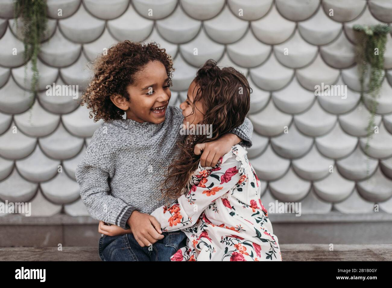Cute siblings smiling and laughing at each other while hugging outside Stock Photo