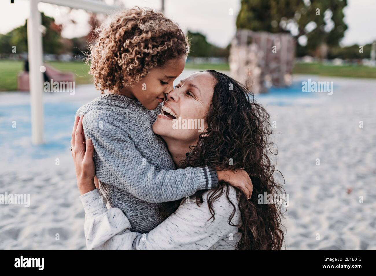 Close up of happy mother and son embracing closely on playground Stock Photo