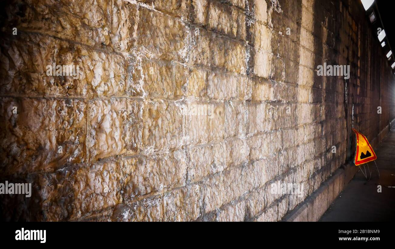 Stone wall with a yellow road plate, Lyon, France Stock Photo