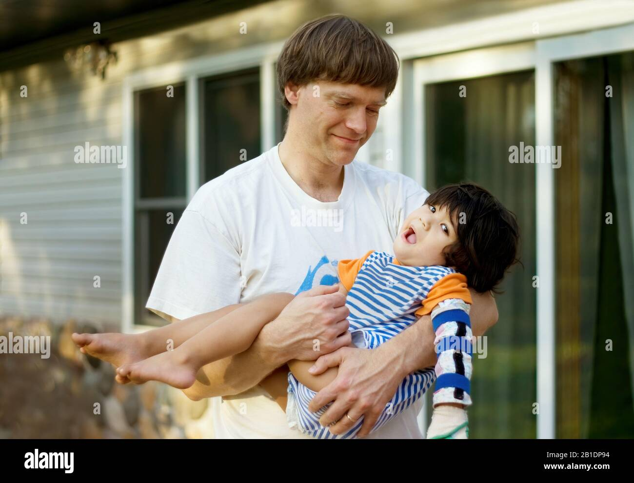 Caucasian father holding disabled biracial son in arms outside of home Stock Photo