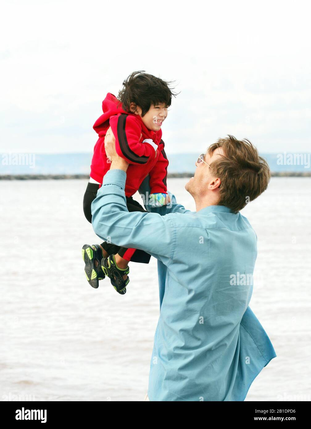 Caucasian father lifting up disabled little boy in his arms overhead outdoors by lake Stock Photo