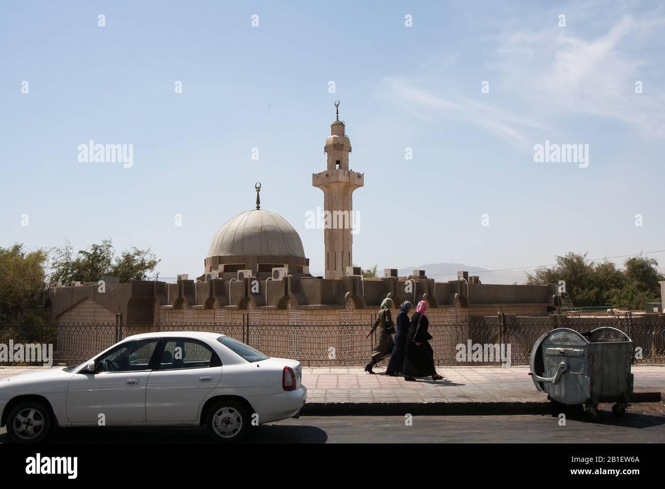 Aqaba, Jordan, April 27, 2009: Women walk on the sidewalk of a road, passing a mosque in Aqaba, Jordan. Stock Photo