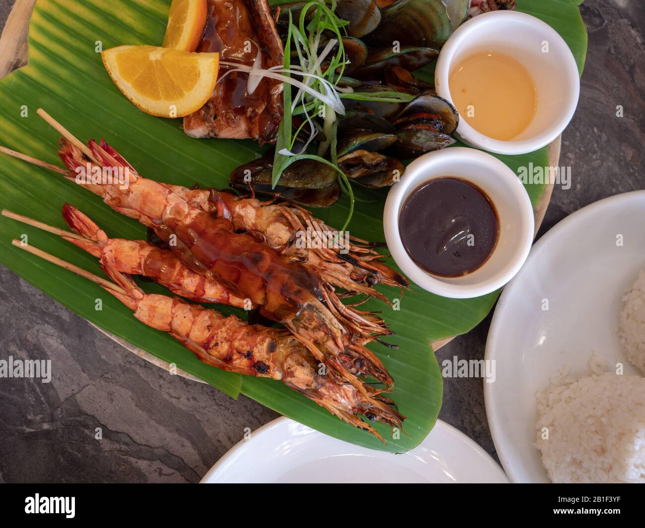 Grilled Seafood Platter With Barbecue Sauce On Banana Leaf Stock Photo Alamy