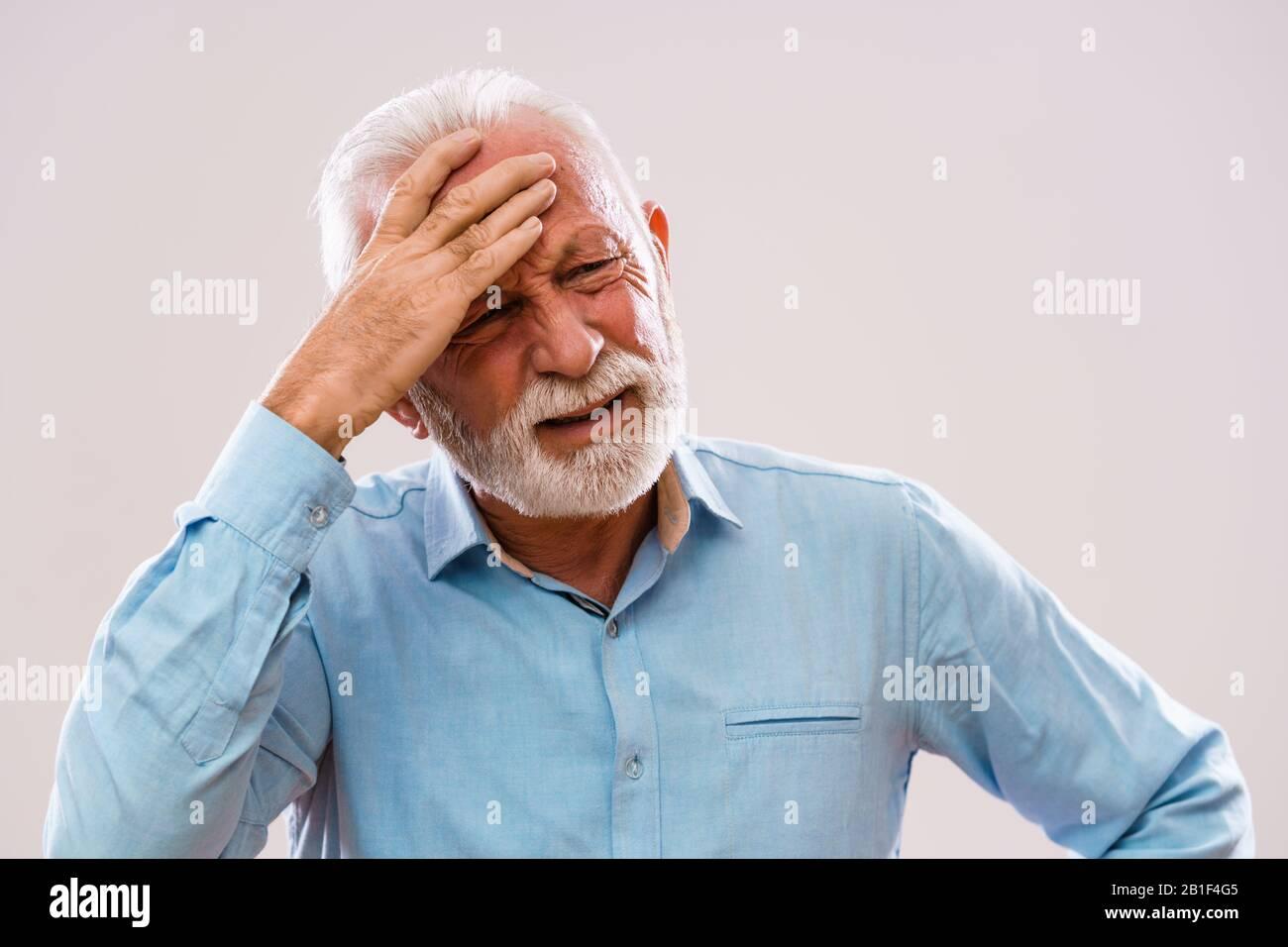 Portrait of senior man who is having headache. Stock Photo