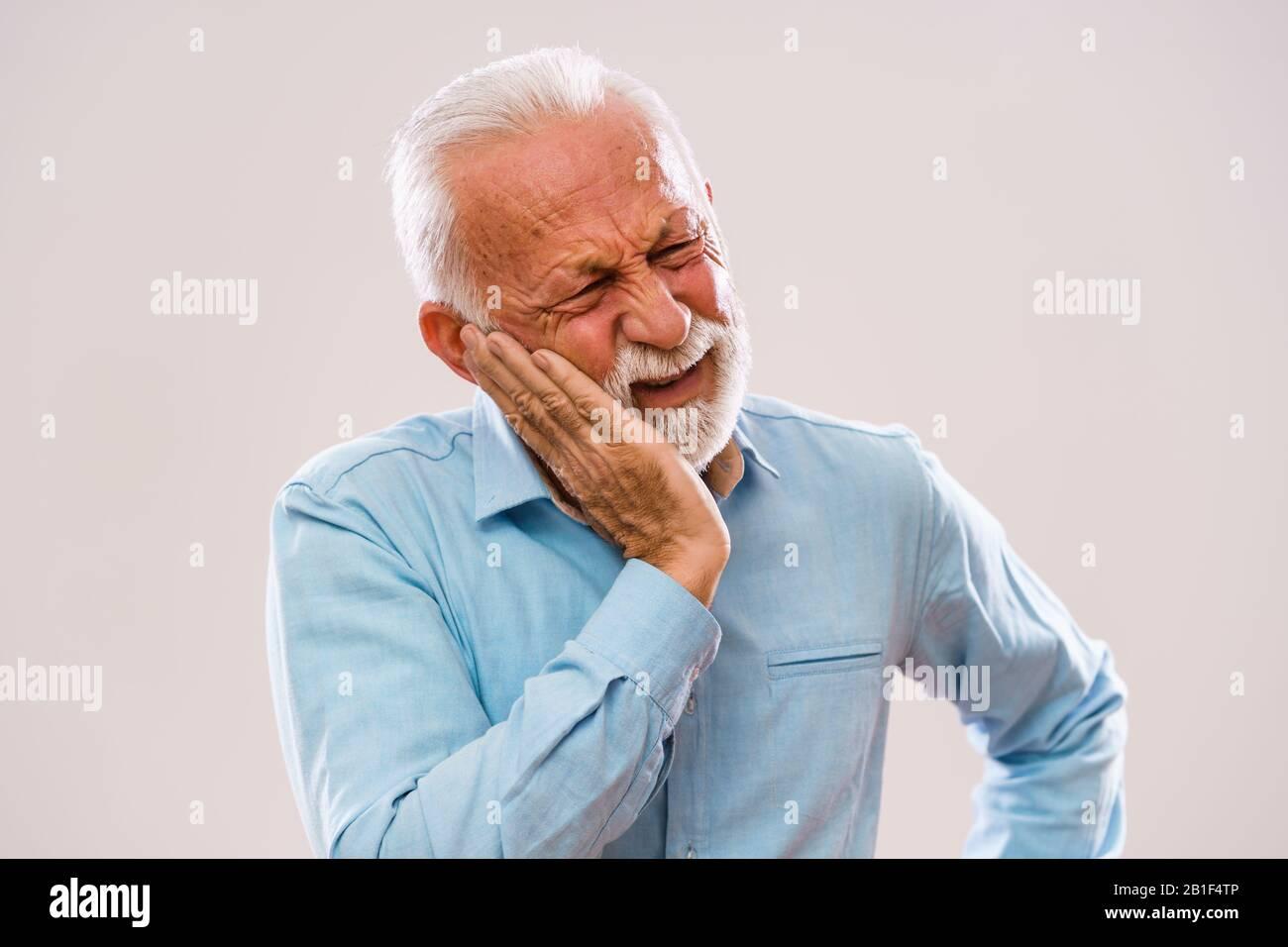 Portrait of senior man who is having toothache. Stock Photo
