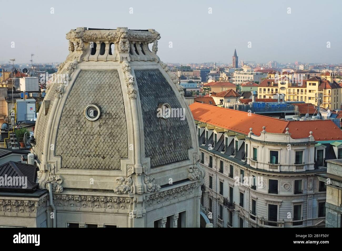 A close view of the balustrade topped roof dome of Palazzo Meroni - lions and floral garlands, oculi windows and the city of Milan in the background Stock Photo