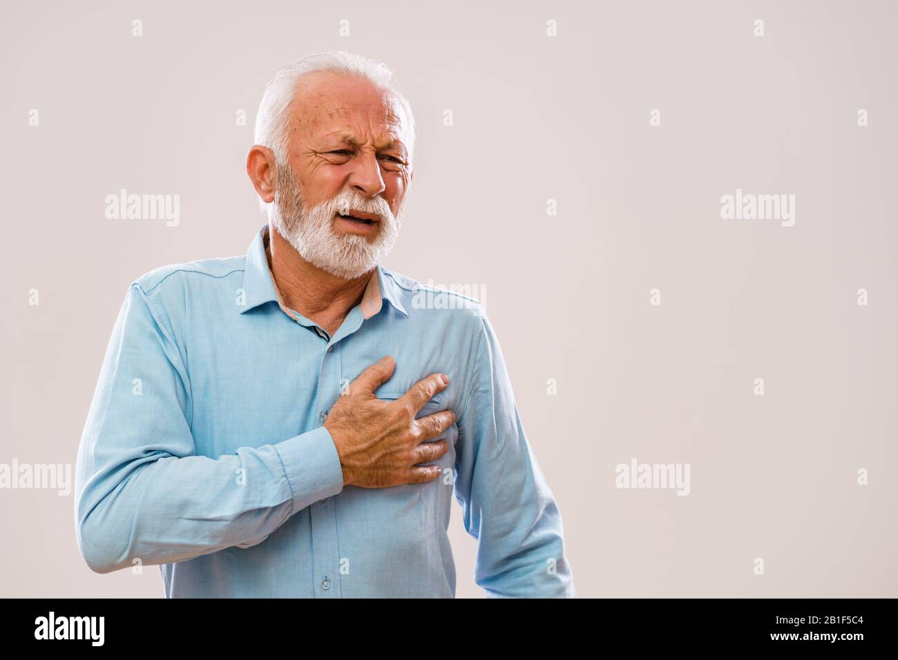 Portrait of senior man who is having pain in his chest. Stock Photo