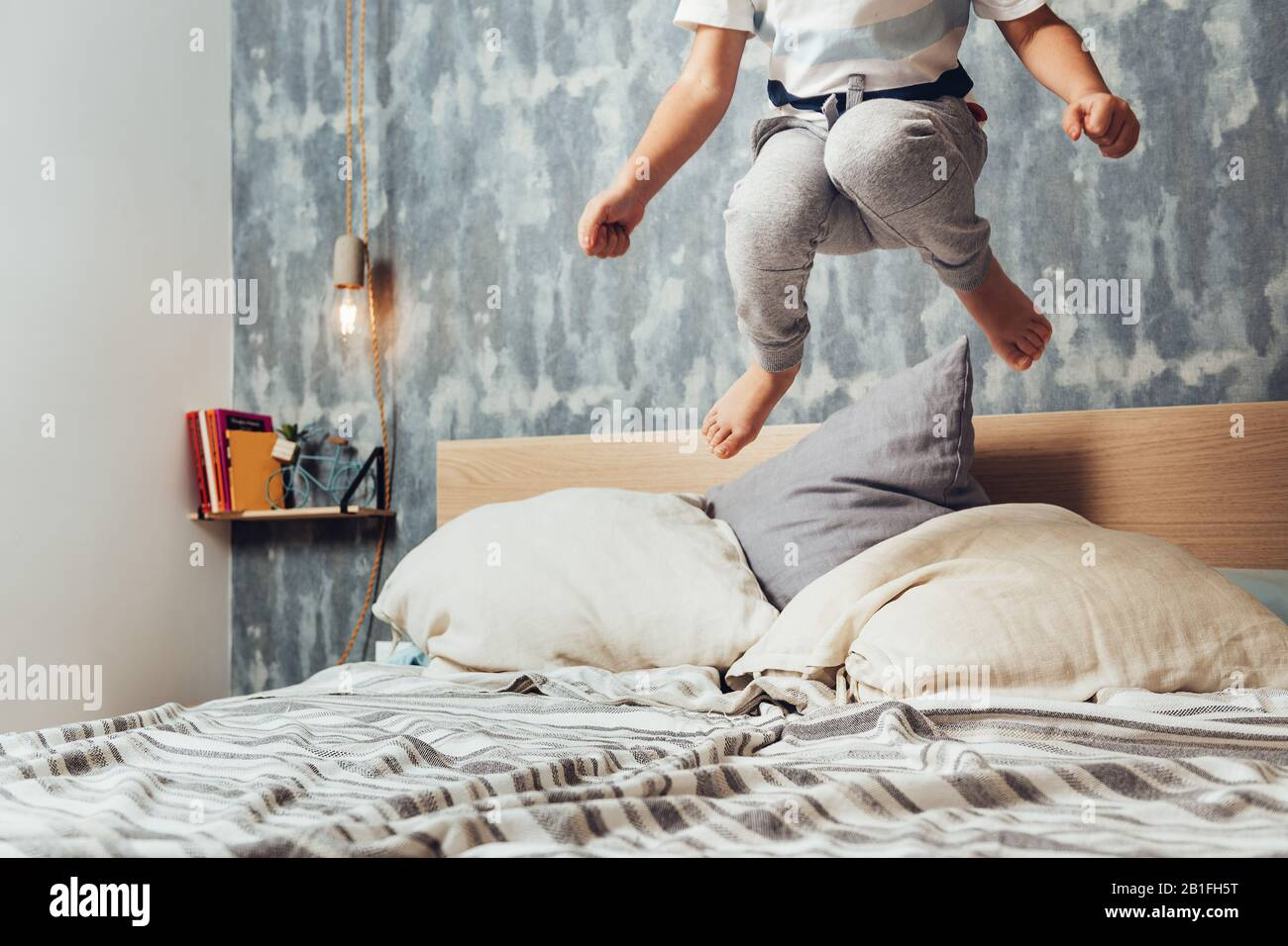 detail of a little girl legs jumping high in her parents bed, home lifestyle concept and happy childhood Stock Photo