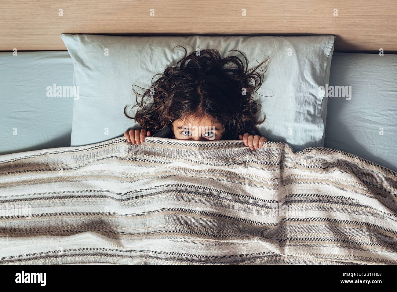 little girl covering her face with a bed sheet, only lets you see her eyes looking at the camera, happy childhood and healthy rest concept Stock Photo