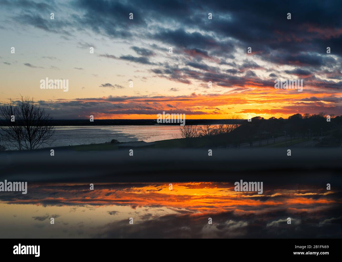 Cloudy sunset over Pegwell Bay, Kent with a foreground reflection in an open fan light window. Stock Photo