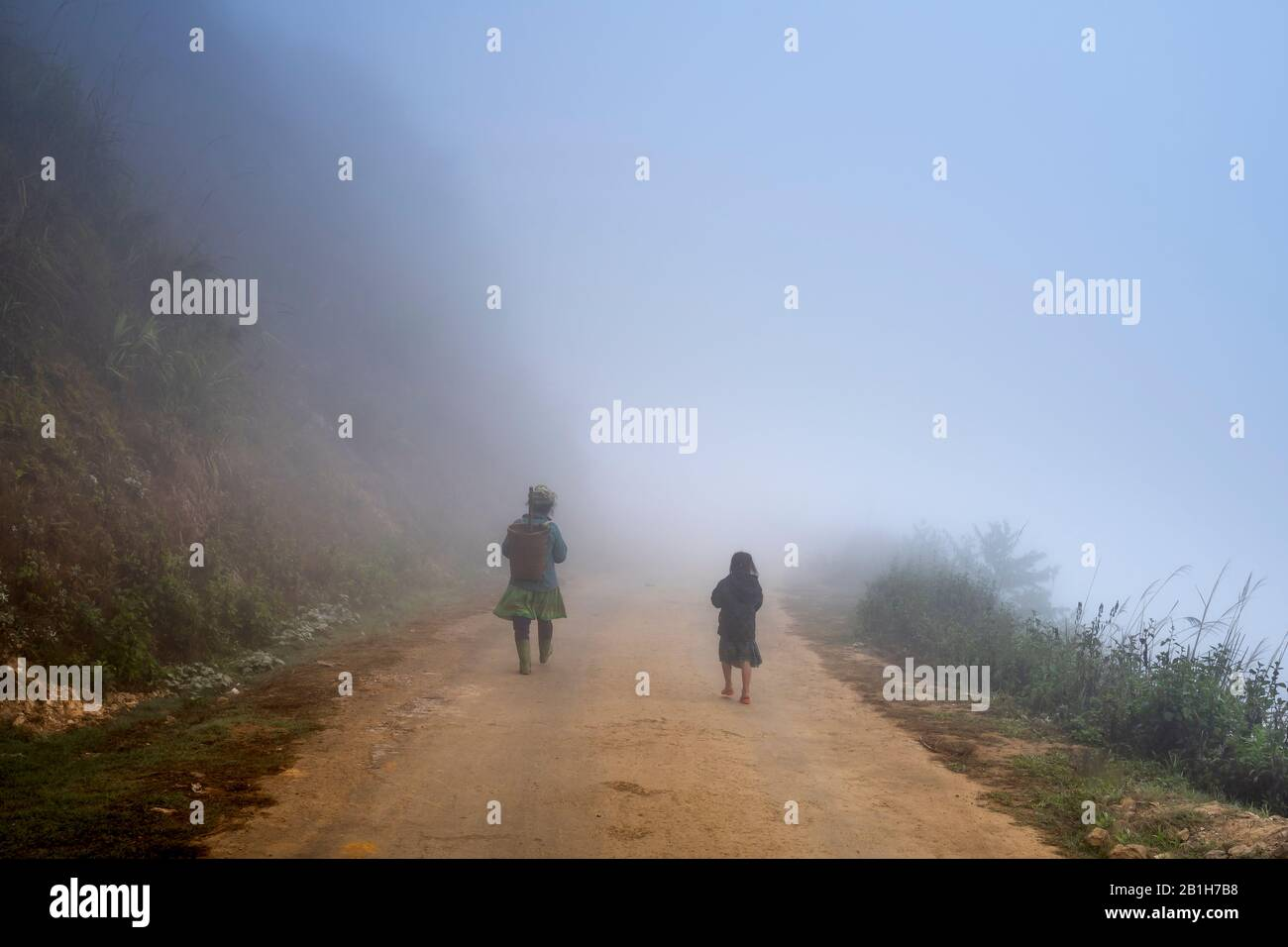 Ta Xua, Son La province, Vietnam - January 22, 2020: The H'mong ethnic woman walking on the village road in fog in Ta Xua, Son La province, Vietnam Stock Photo