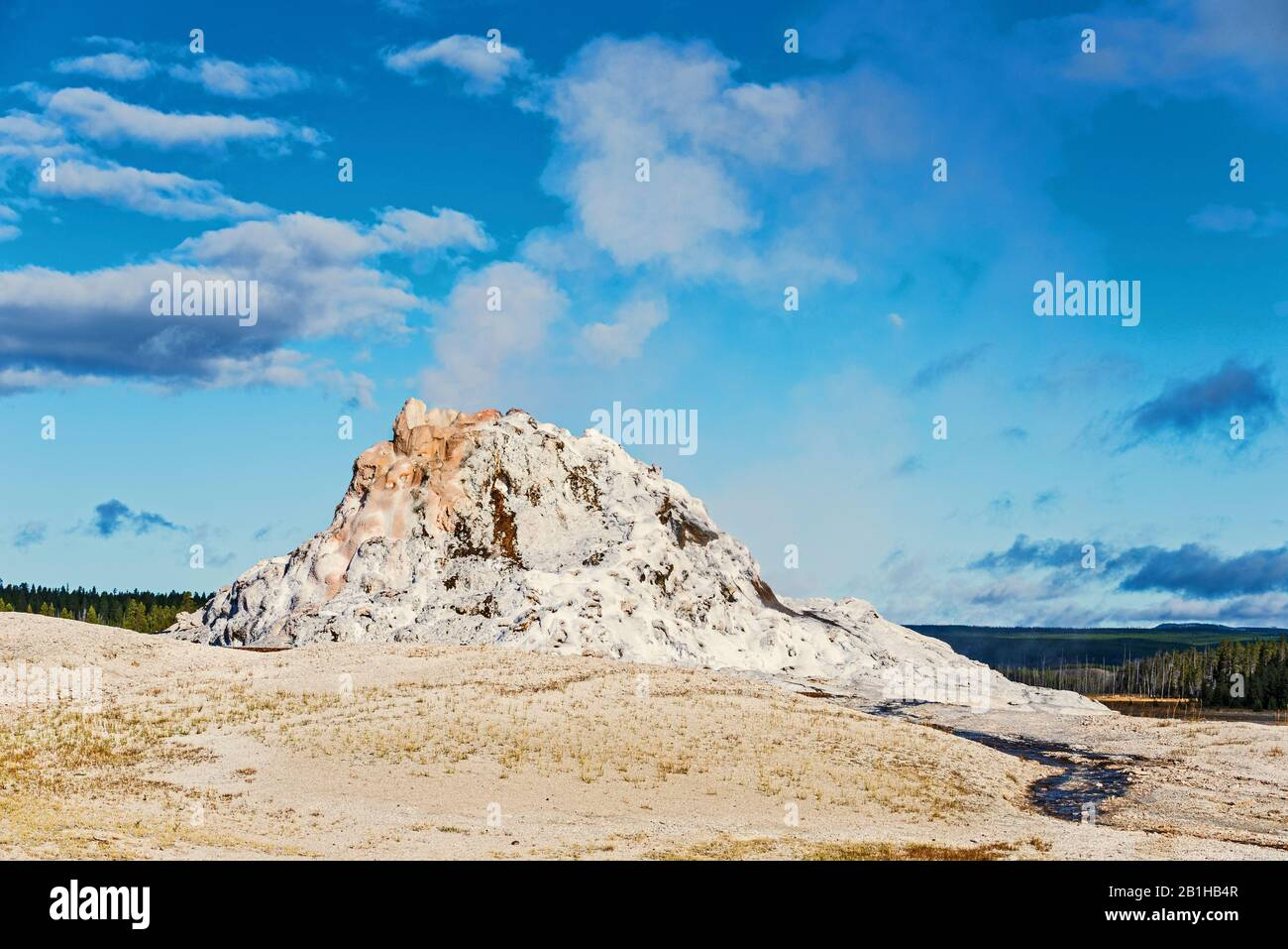 Steaming geyser rock formation against a blue sky with white clouds. Stock Photo