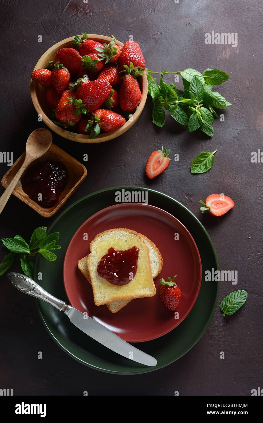 Toasts with strawberry jam for breakfast, rustic style Stock Photo