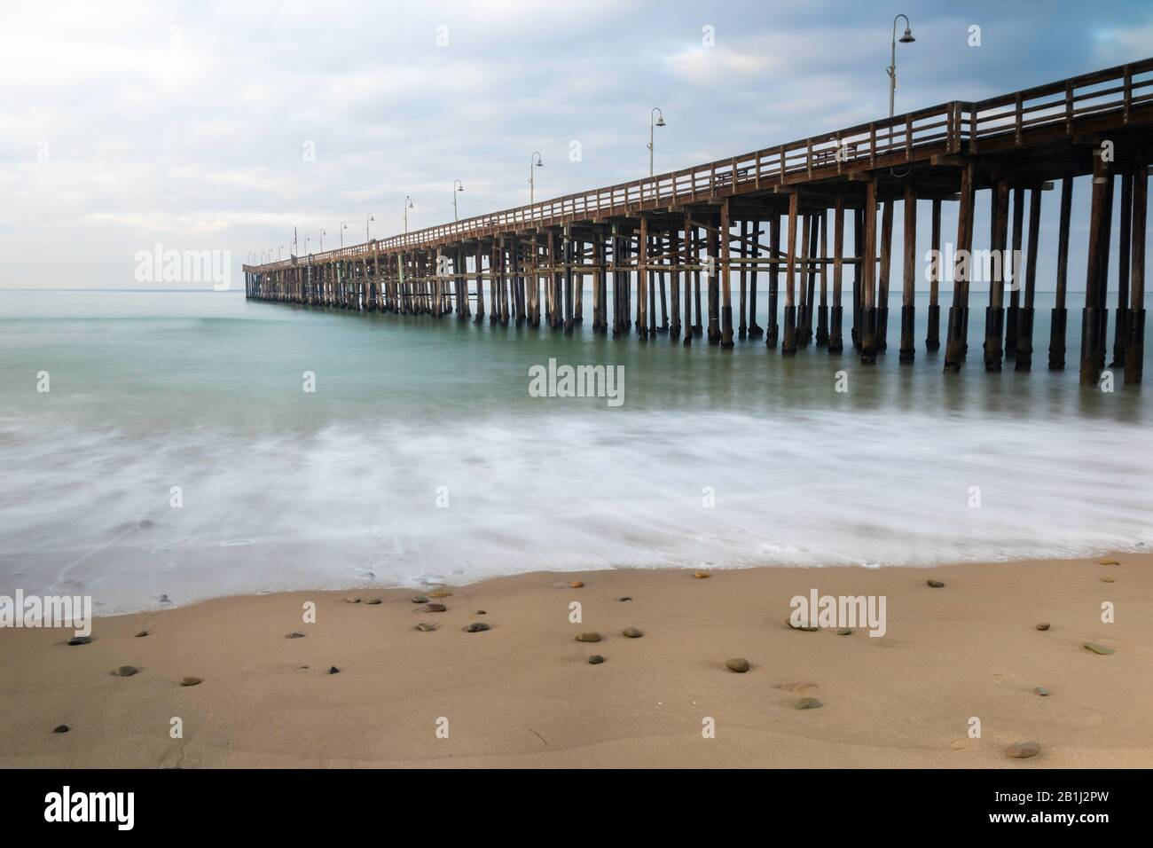 Pier at Ventura, California; view from beach, extending into the water. Green ocean, cloudy sky. Stock Photo