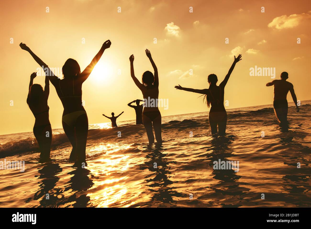 Big group of happy peoples stands at sunset sea beach. Silhouettes with raised arms Stock Photo