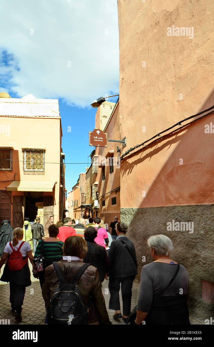 Marrakesh, Morocco - November 22nd 2014: Group of unidentified tourists by sightseeing in narrow street in old precinct, woman with traditional veil Stock Photo