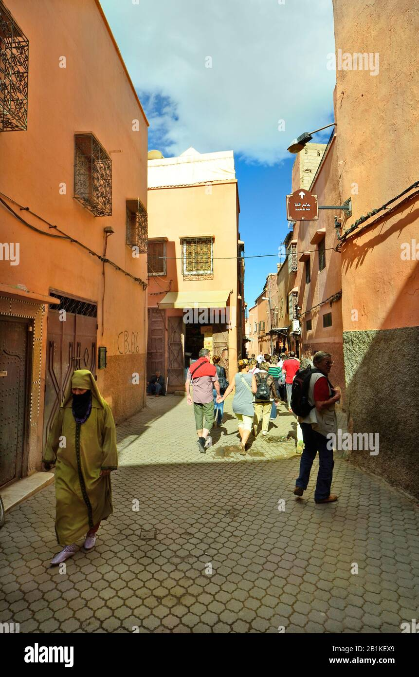 Marrakesh, Morocco - November 22nd 2014: Unidentified tourists by sighseeing in narrow street in the old precinct and woman in traditional kaftan with Stock Photo