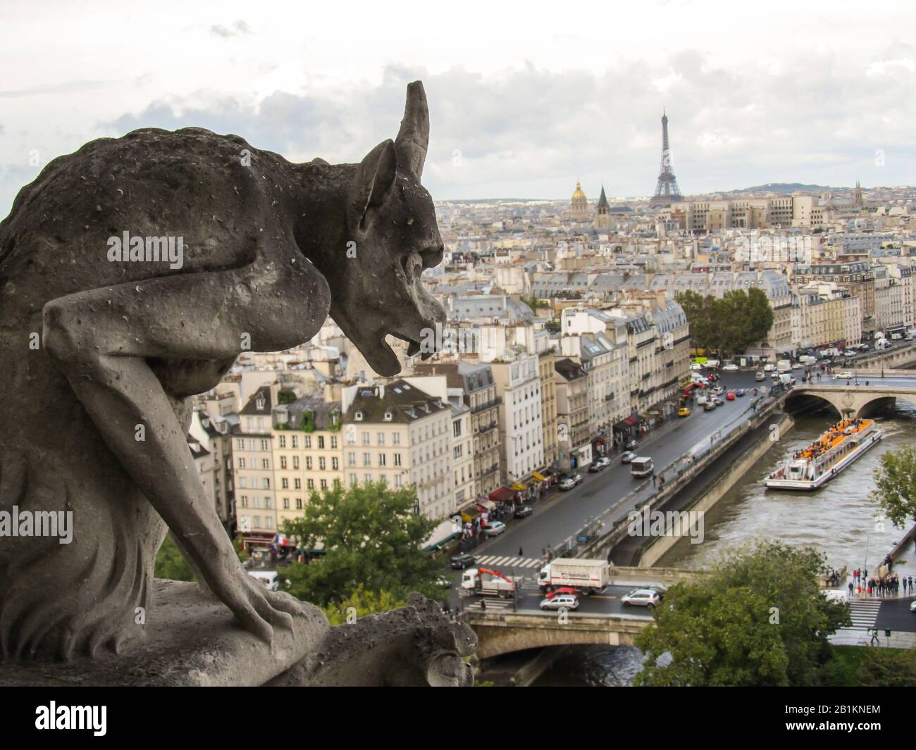 View of the Paris cityscape, including the Eiffel Tower and the River Seine, from one of the towers of Notre-Dame, with a stone carved Gargoyle in the Stock Photo