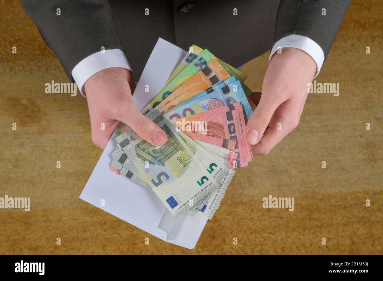 Hand, Geldschumschlag, Symbolfoto Lohntüte, Studioaufnahme Stock Photo