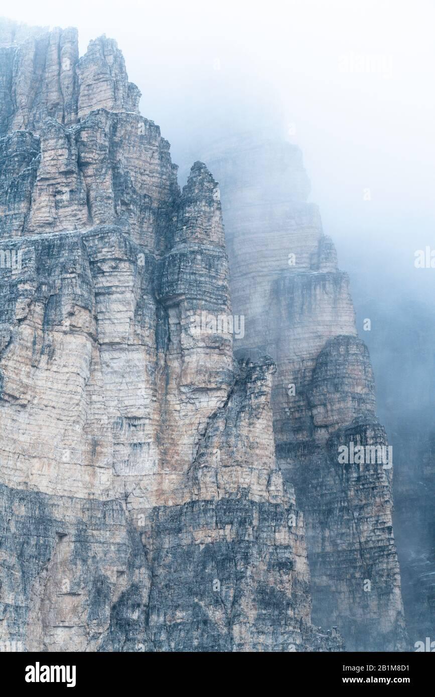 Fog over the tall rocks of Tre Cime di Lavaredo, Sesto Dolomites, South Tyrol, Italy Stock Photo