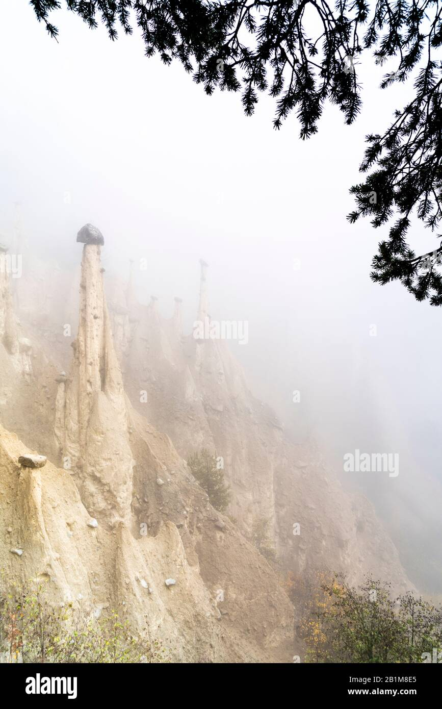 Foggy sky in autumn over the Earth Pyramids rock formations, Perca/Percha, province of Bolzano, South Tyrol, Italy Stock Photo