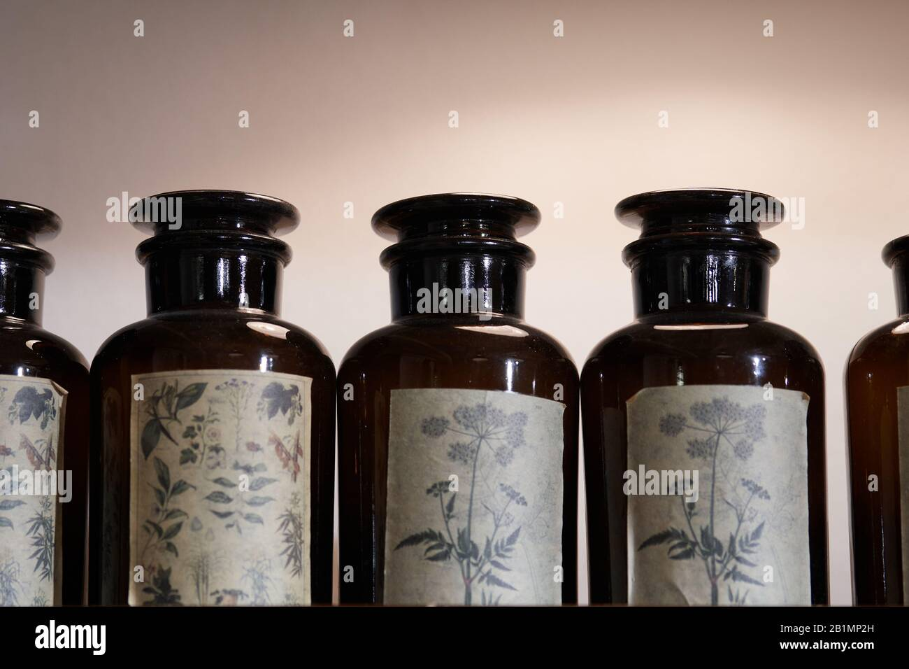 A row of vintage brown glass apothecary jars with used labels displaying herbal drawings Stock Photo