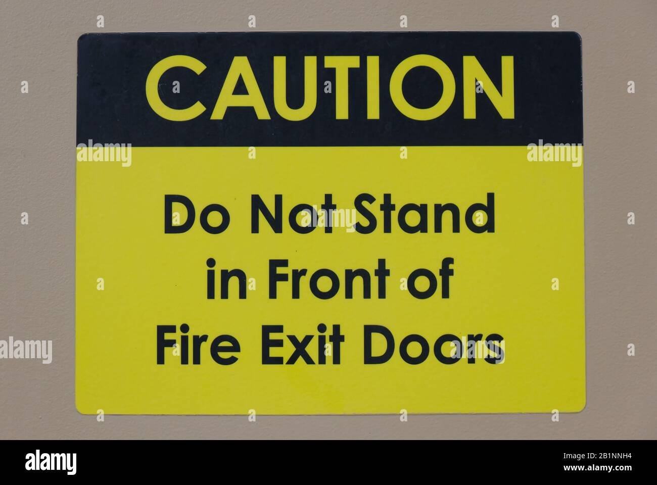 """""""Caution: Do not stand in front of Fire Exit Doors"""" warning text and sign inform to keep the doorway accessible Stock Photo"""
