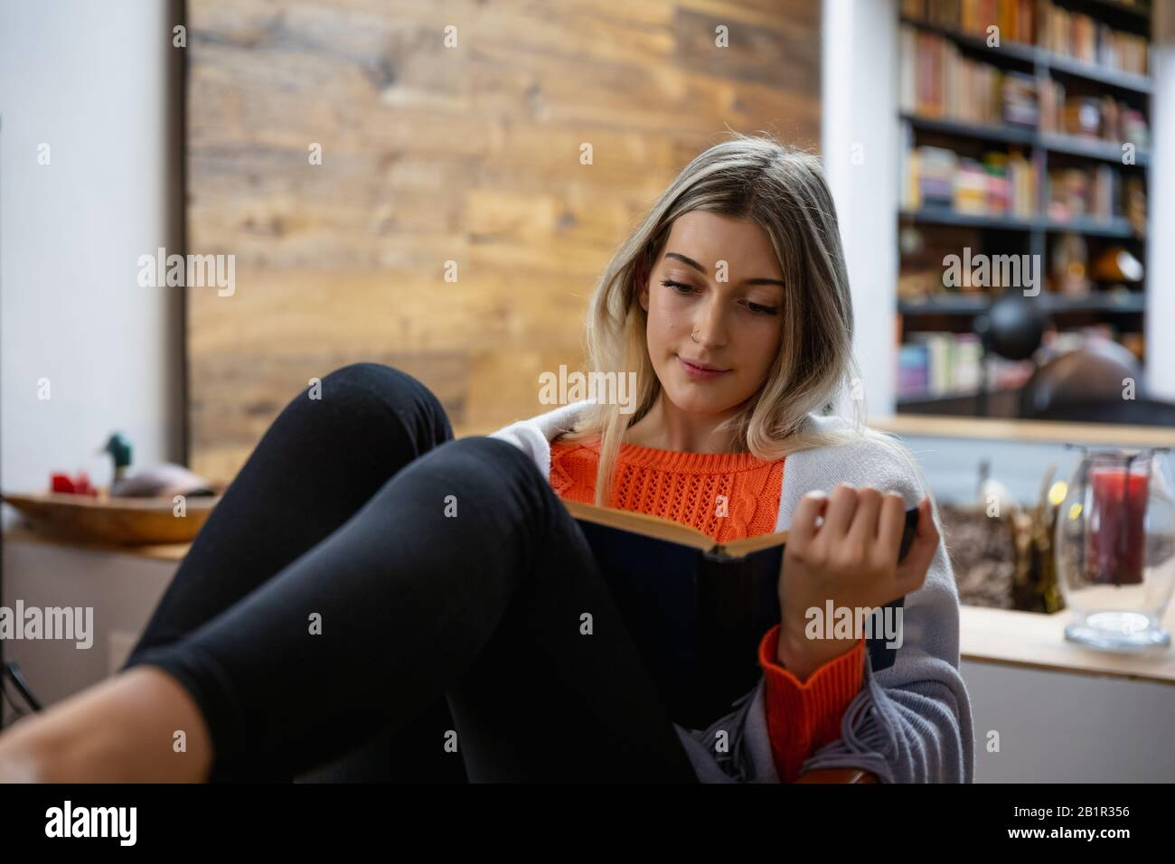 Young woman reading a book home Stock Photo
