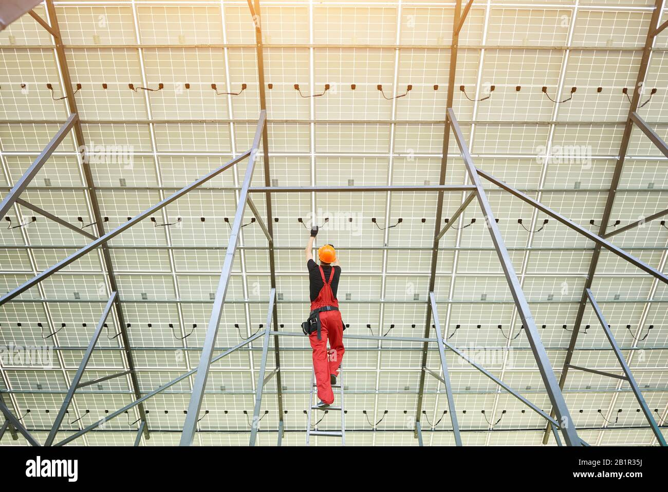 Installing and wiring of solar photo voltaic panels. Back view of worker in orange uniform connecting solar panels at the station. Ecology power conservation concept. Stock Photo