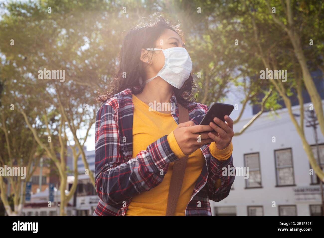 Woman wearing a Corona Virus face mask and using her phone Stock Photo