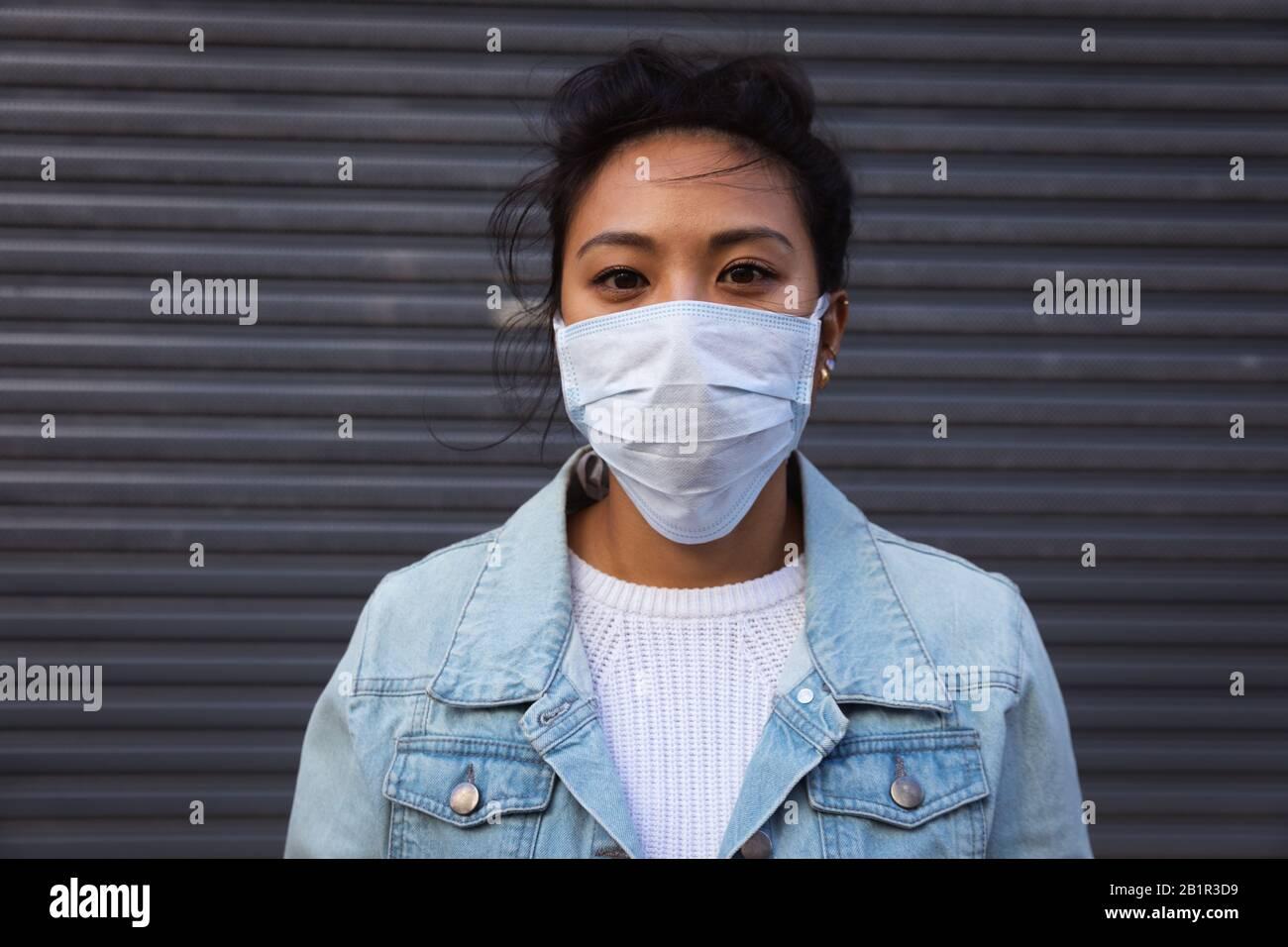 Woman wearing a Corona Virus face mask and looking at camera Stock Photo