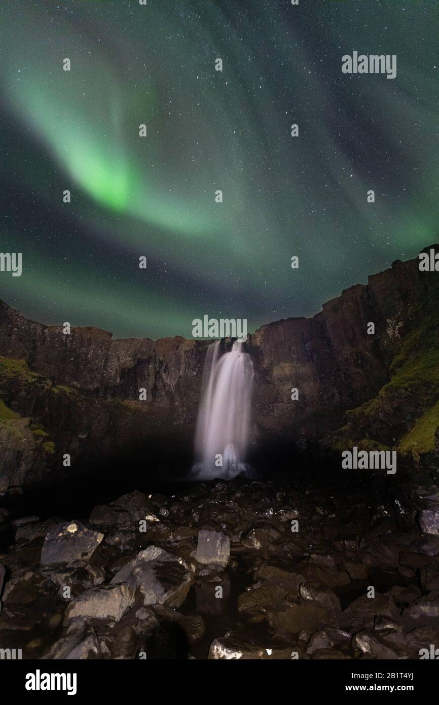 Northern lights over Gufufoss waterfall, East Iceland. Stock Photo