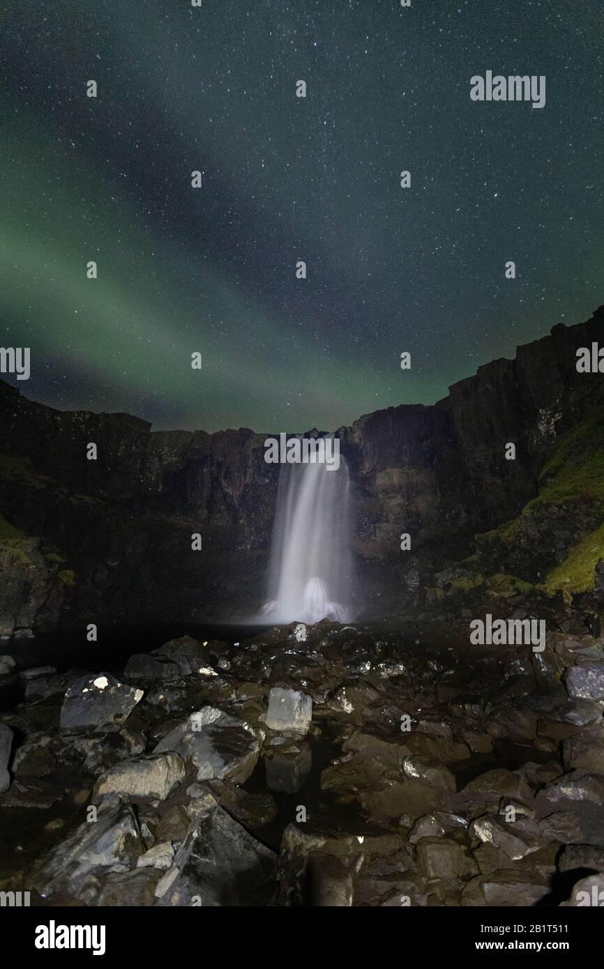 Northern lights over Gufufoss waterfall, East Iceland. Stock Photo