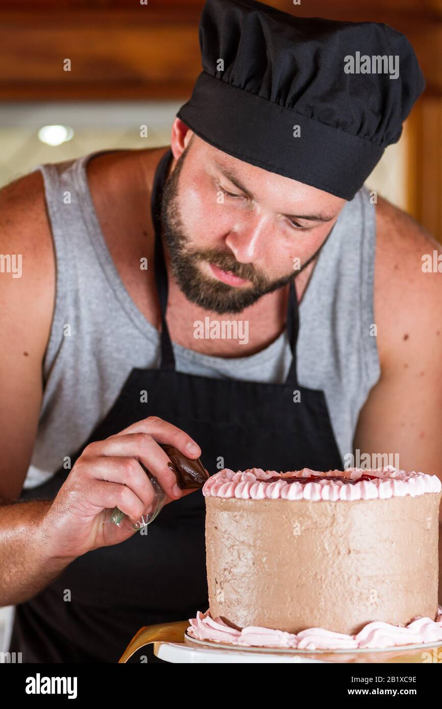 Peachy Male Baker Decorating A Chocolate Birthday Cake With Strawberry Funny Birthday Cards Online Overcheapnameinfo