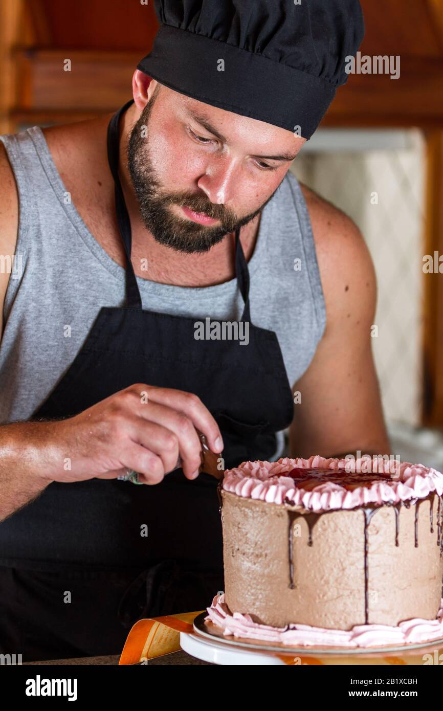 Admirable Male Baker Decorating A Chocolate Birthday Cake With Strawberry Funny Birthday Cards Online Overcheapnameinfo